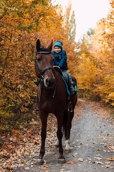 Garotinho sentado no cavalo e sorrindo