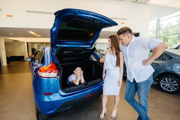 Garotinho sentado no porta-malas enquanto seus pais escolhem um carro novo