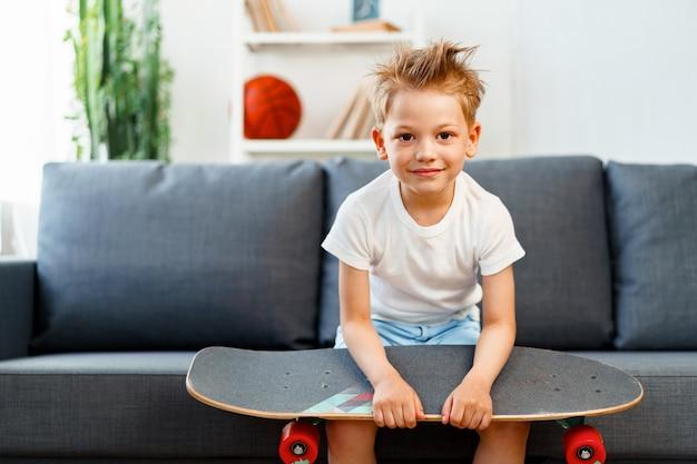 Garotinho sentado no sofá em casa segurando um skate, retrato