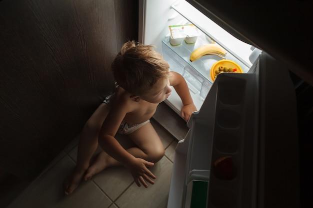 Garotinho sentado perto da geladeira aberta à noite