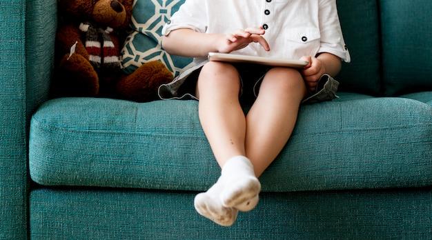 Garotinho sentou-se em um sofá usando tablet digital