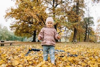 Garotinho sorridente em pé na folhagem de outono no parque