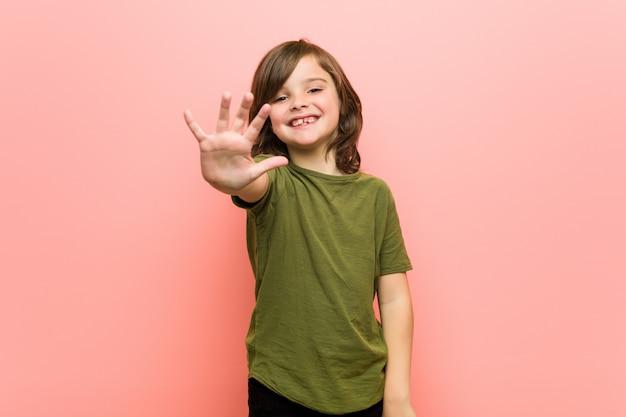 Garotinho sorrindo alegre mostrando número cinco com os dedos.