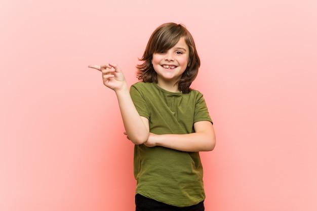 Garotinho sorrindo alegremente apontando com o dedo indicador fora.