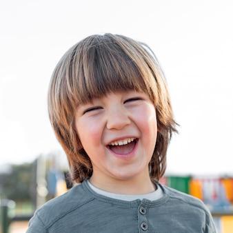 Garotinho sorrindo ao ar livre