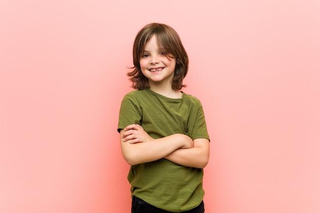 Garotinho sorrindo confiante com braços cruzados.