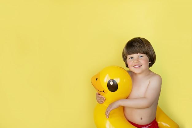 Garotinho, sorrindo e abraçando a piscina inflável pato amarelo flutuar com espaço de cópia sobre o fundo amarelo