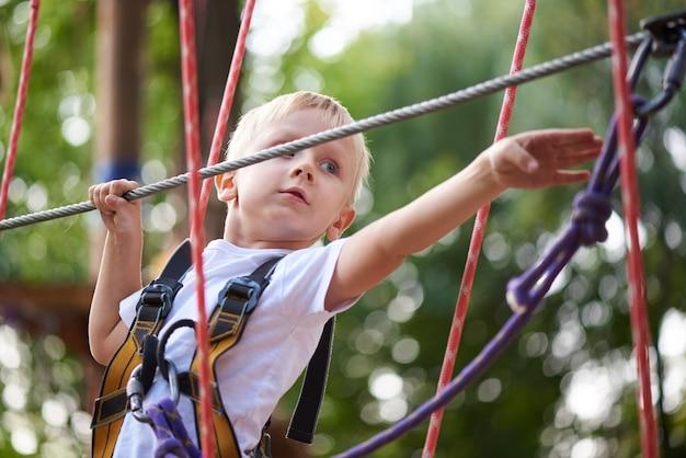 Garotinho supera o obstáculo no parque de corda.