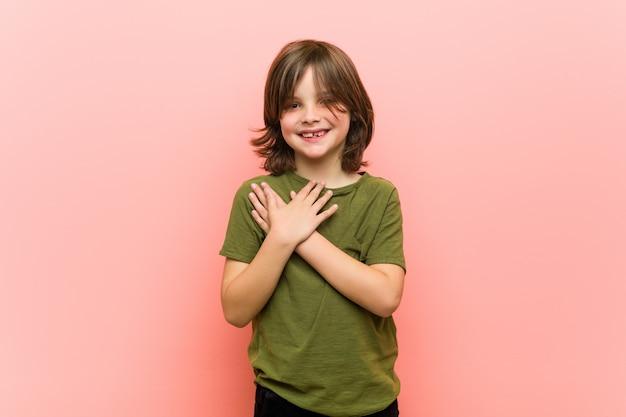 Garotinho tem expressão amigável, pressionando o peito palm. ame .