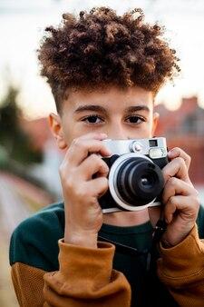 Garotinho tirando uma foto com sua câmera lá fora