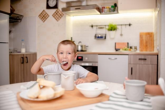 Garotinho toma café da manhã. cozinha leve, mesa de madeira e pessoal da cozinha