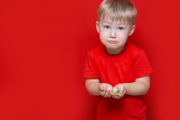 Garotinho triste segurar um monte de pílulas nas mãos