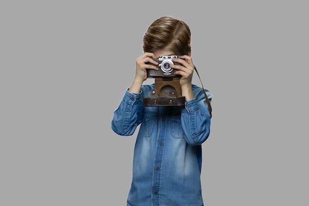 Garotinho usando a velha câmera retro. linda criança na jaqueta jeans tirando foto com a câmera fotográfica envelhecida contra um fundo cinza. jovem fotógrafo bonito.