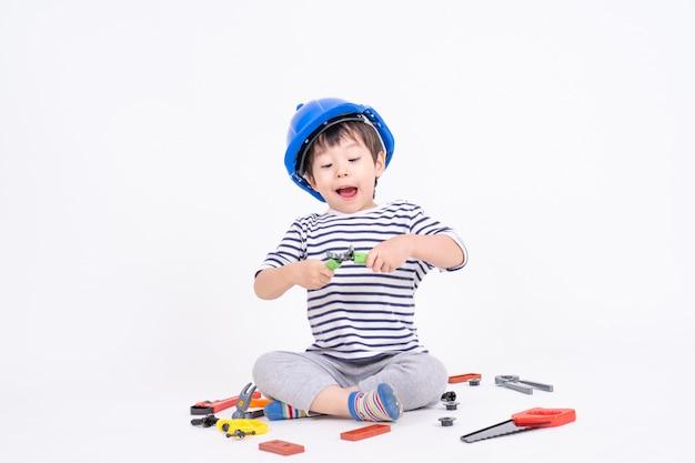 Garotinho, usando capacete azul, sentado e brincando com o brinquedo de equipamento de construção em branco