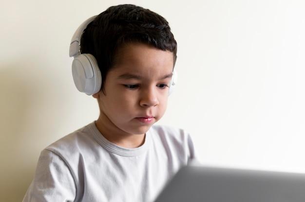 Garotinho usando laptop na cama com fones de ouvido