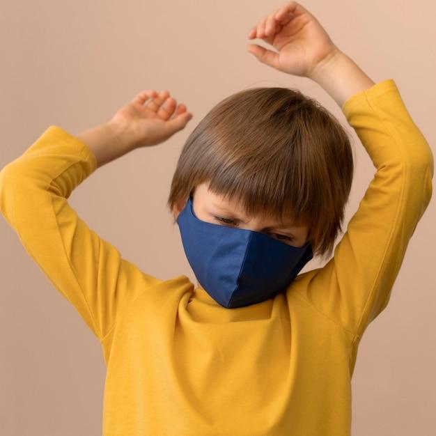 Garotinho usando máscara médica dentro de casa