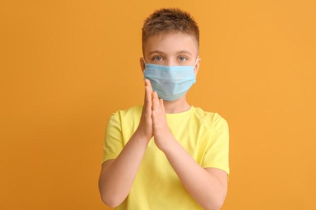 Garotinho usando máscara protetora laranja
