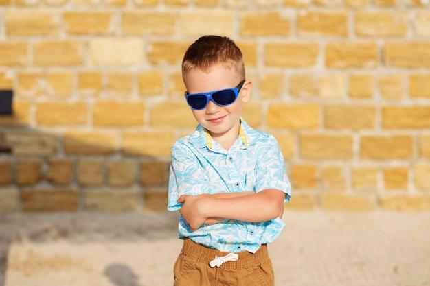 Garotinho usando óculos escuros espelho azul contra a parede de tijolos amarelos.