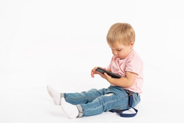 Garotinho, usando telefone celular. criança brincando no smartphone. tecnologia, aplicativos móveis, aconselhamento para crianças e pais, estilo de vida