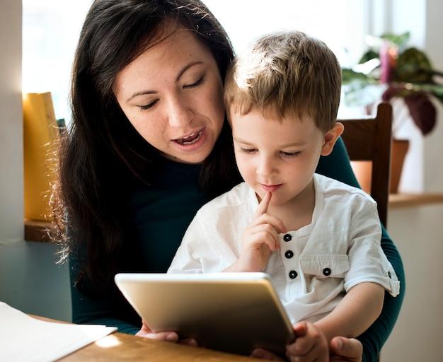 Garotinho usando um tablet com a mãe