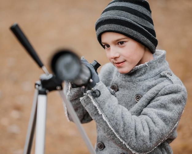 Garotinho usando um telescópio de frente