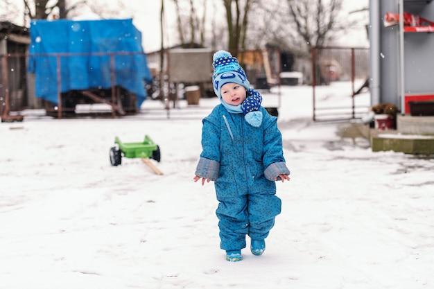 Garotinho vestido com roupas de inverno, andando na neve e congelando.