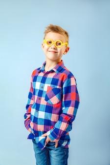 Garotinho, vestindo camisa xadrez colorida, jeans azul, óculos de plástico se divertindo no estúdio