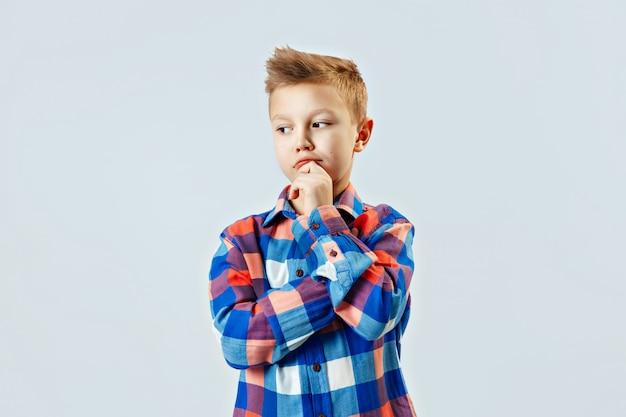 Garotinho, vestindo camisa xadrez colorida, óculos de plástico, pensando, fazendo escolher no estúdio