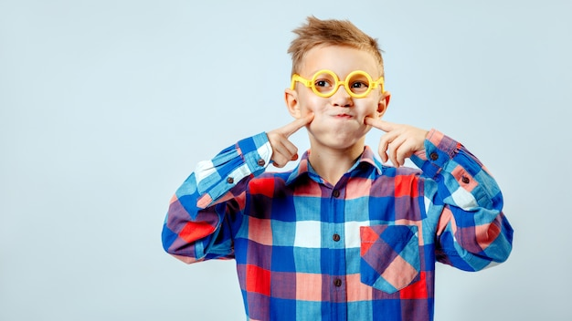 Garotinho, vestindo camisa xadrez colorida, óculos de plástico se divertindo no estúdio