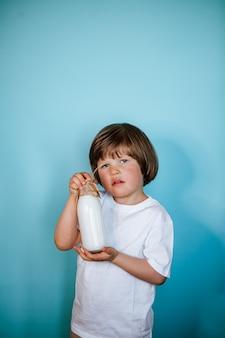 Garotinho, vestindo camiseta branca, segurando a garrafa de leite na parede azul