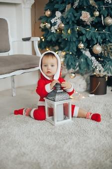 Garotinho vestindo fantasia de papai noel com árvore de natal