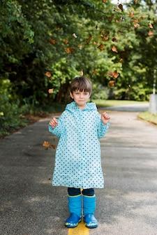 Garotinho, vestindo um casaco de chuva