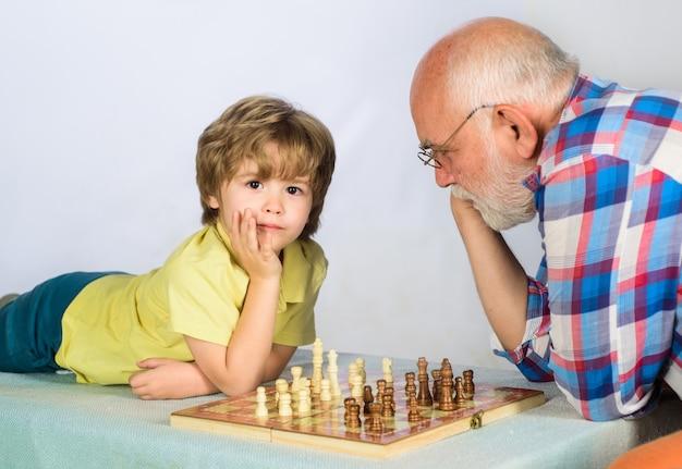 Garotinho xeque-mate, pense ou planeje o jogo de xadrez, criança, garoto jogando xadrez com os jogos do avô e