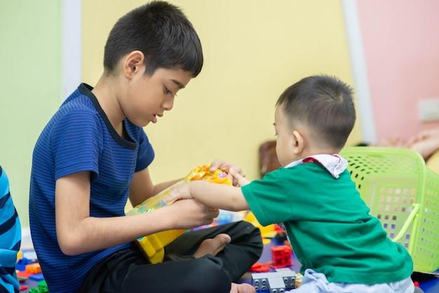Garotinhos brincando de brinquedo juntos na sala