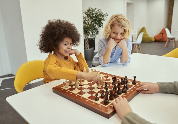 Garotinhos diversos e alegres sentados à mesa jogando xadrez na escola
