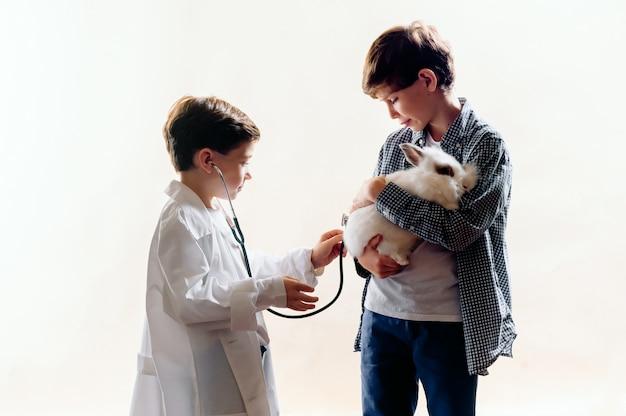 Garotinhos estão jogando veterinário com um coelho. conceito veterinário de amor animal