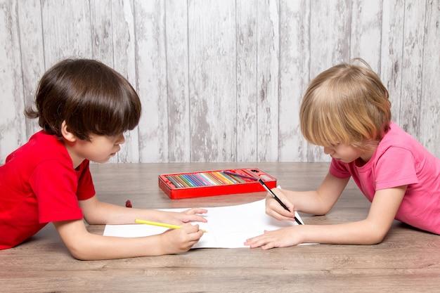 Garotinhos no desenho de camisetas rosa e vermelho