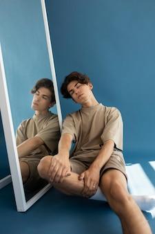 Garoto adolescente bonito sentado ao lado de um espelho
