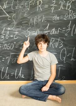 Garoto adolescente bonito tendo uma ideia em matemática