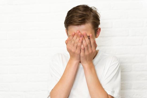 Garoto adolescente cobrindo o rosto com a mão, cara chorando, esconde emoções, jovem deprimido