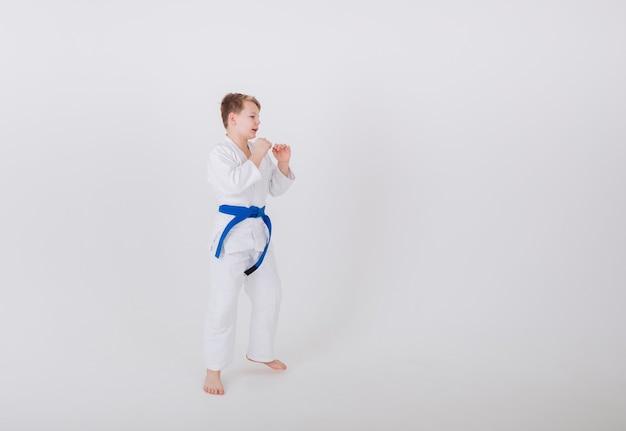 Garoto adolescente em um quimono branco parado de lado em uma parede branca