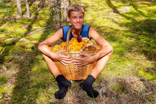 Garoto adolescente feliz sentado na floresta de outono com uma grande cesta de chanterelles e cogumelos porcini
