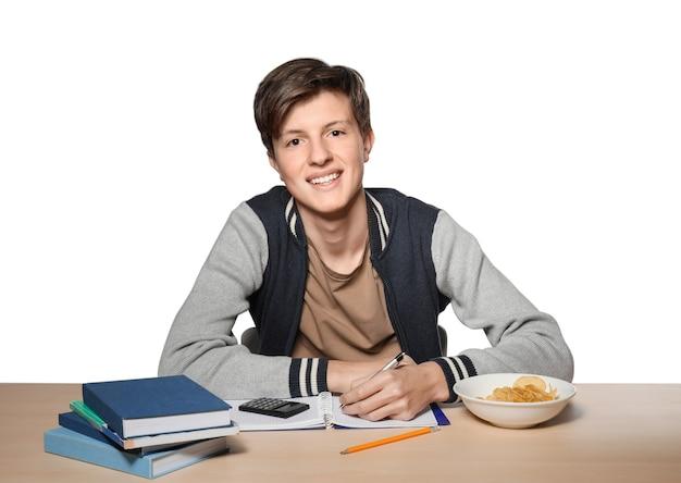 Garoto adolescente fofo fazendo lição de casa contra uma superfície branca