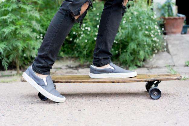 Garoto adolescente jogando skate no parque público