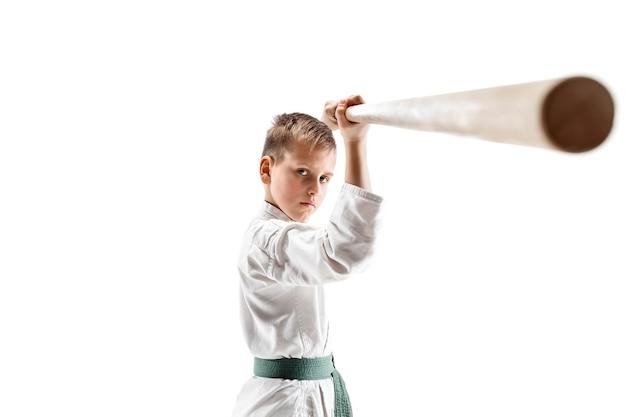 Garoto adolescente lutando com uma espada de madeira no treinamento de aikido na escola de artes marciais
