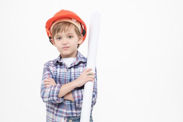 Garoto adorável vestido como capataz de capacete laranja e camisa segurando rascunhos de papel nas mãos, olhando para a câmera