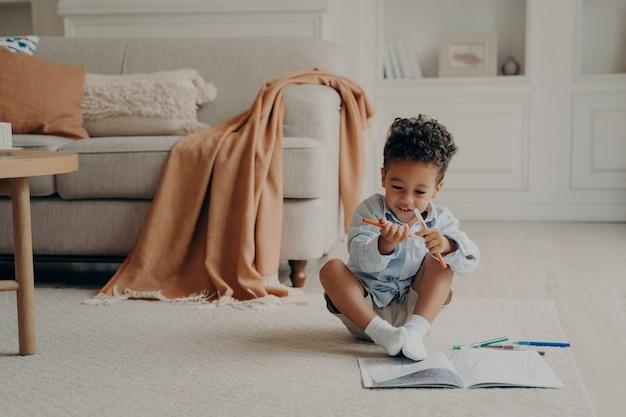 Garoto afro-americano fofo com livro de colorir sentado no chão em uma aconchegante sala de estar