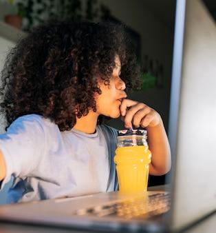 Garoto afro bonito bebendo suco de laranja enquanto usa o computador em casa