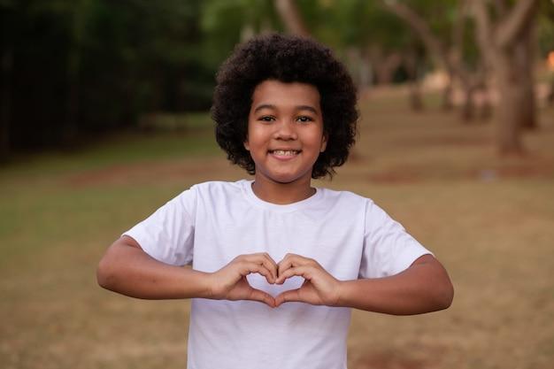 Garoto afro fazendo coração com a mão