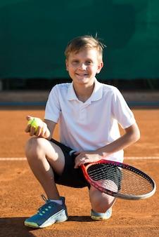 Garoto agachado no campo de ténis
